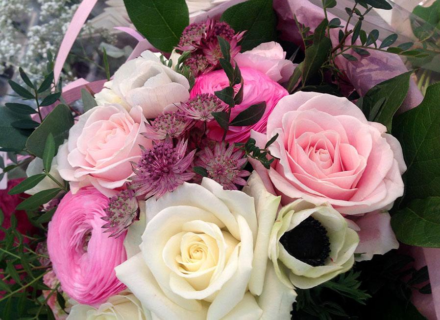 Uppvakta med en blomsterbukett i rosa och vita toner.